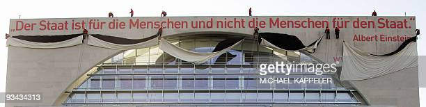 Workers unveil a giant banner hanging on a federal administrative building spelling out a quote by Germanborn Swiss physicist Albert Einstein in...