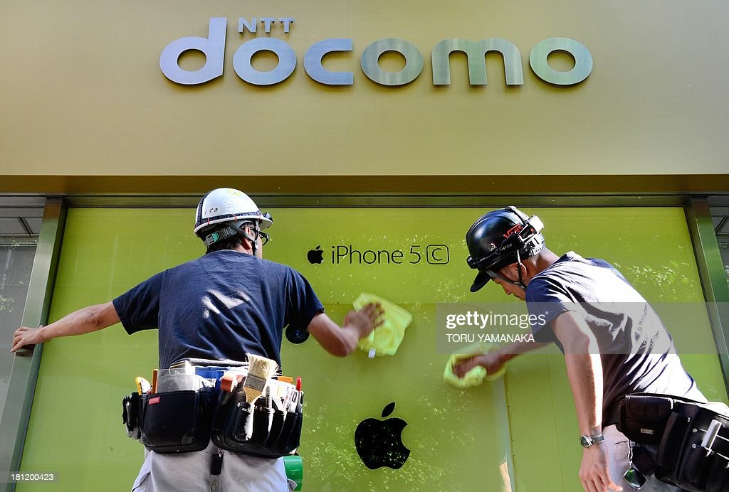 Workers unveil windows with a logo of Apple's iPhone at a shop of Japan's biggest mobile carrier NTT Docomo in Tokyo on September 20, 2013. Apple's new iPhone 5s and 'cheap' 5C models on September 20 went on sale in Japan. AFP PHOTO/Toru YAMANAKA