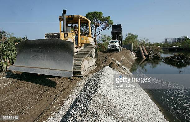 Workers use a bulldozer to smooth over gravel while repairing the London Canal levee which was breached during Hurricane Katrina September 21 2005 in...