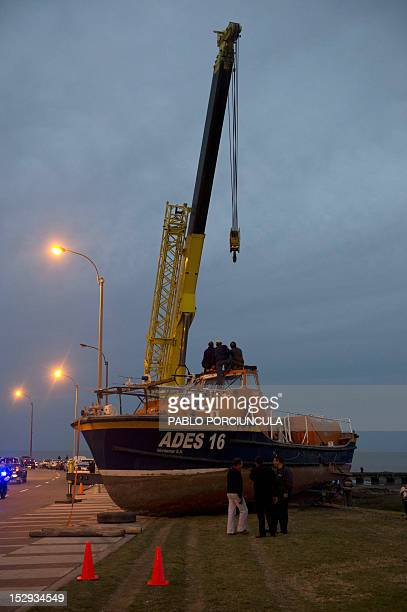 Workers use a crane to lift a coastguards vessel in Montevideo on September 28 days after it was swept on land during a fierce storm Strong gusts...