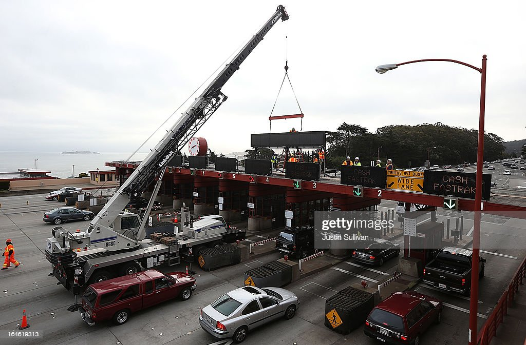 Workers use a crane to lower a new LED sign onto the top of the Golden Gate Bridge toll plaza on March 25, 2013 in San Francisco, California. Workers are making last minute changes to the Golden Gate Bridge toll plaza in preparation of making the iconic bridge the first major toll bridge in the nation to go to all electronic tollbooths. The entire staff of full time toll collectors will be replaced by the automated booths starting on March 27.