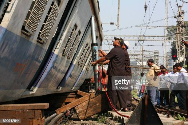 Workers use a hydraulic jack to lift as a Kalyan bound local train derails just a few metres away after leaving CST Station morning
