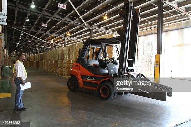 Workers use a Linde AG forklift truck to move packages of paper cellulose sheets in a warehouse ahead of distribution at the Ngodwana wood mill...