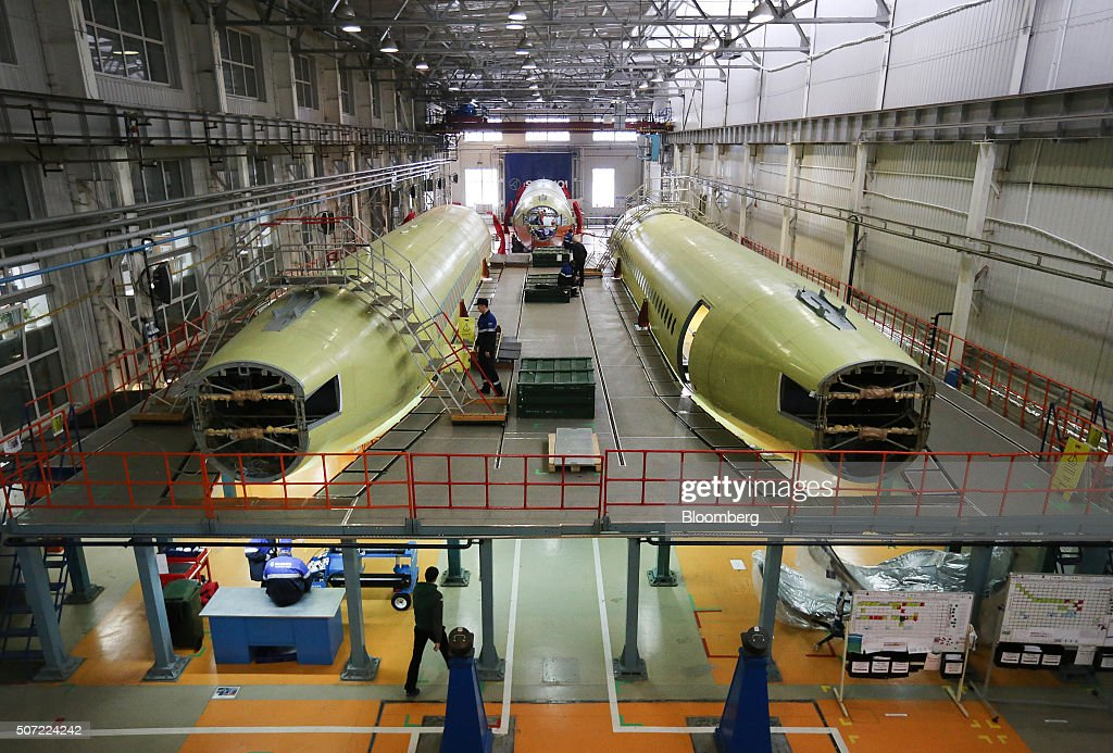 Workers use a raised platform during the construction of fuselage sections of Sukhoi Superjet 100 aircraft in the Sukhoi Civil Aircraft Co final...