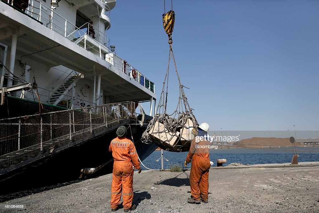 Workers use a winch as they load goods onto a cargo ship from the dockside at Thessaloniki port operated by Thessaloniki Port Authority SA in...