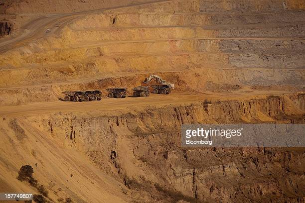 Workers use Caterpillar Inc trucks and heavy digging machines to excavate ore from the open pit at Katanga Mining Ltd's KOV copper and cobalt mine in...