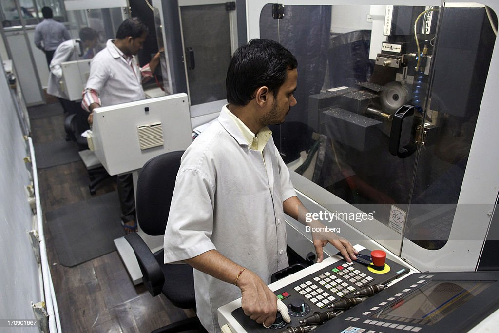 Workers use computer numerical control (CNC) machines at the Kama Schachter Jewelry Pvt Ltd. diamond studded gold and platinum manufacturing facility in Mumbai, India, on Wednesday, June 19, 2013. India's exports of diamonds and gold jewelry grew 5.2% to $6.1 billion in April and May, says the Gem & Jewellery Export Promotion Council on June 18, 2013. Photographer: Adeel Halim/Bloomberg via Getty Images