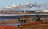 Workers use heavy machinery in the tailings pond at the Syncrude oil sands extraction facility near the town of Fort McMurray in Alberta Province...
