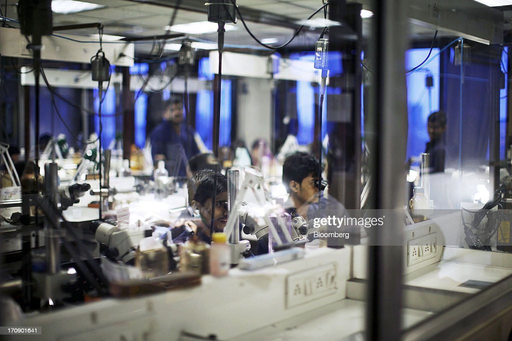 Workers use microscopes to inspect jewelry at the Kama Schachter Jewelry Pvt Ltd. diamond studded gold and platinum manufacturing facility in Mumbai, India, on Wednesday, June 19, 2013. India's exports of diamonds and gold jewelry grew 5.2% to $6.1 billion in April and May, says the Gem & Jewellery Export Promotion Council on June 18, 2013. Photographer: Adeel Halim/Bloomberg via Getty Images