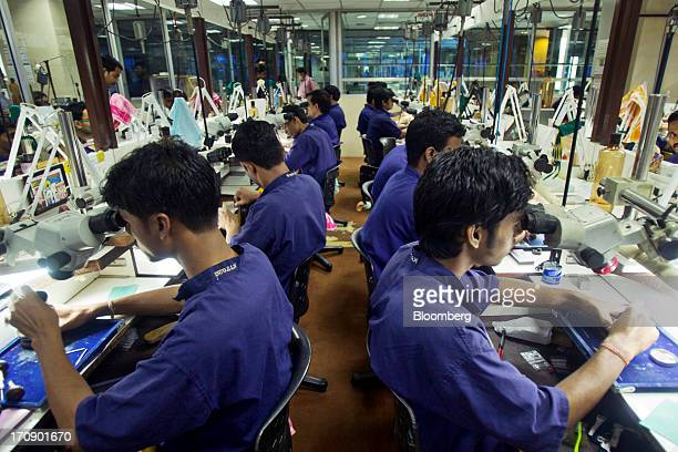 Workers use microscopes to inspect jewelry in the metal setting unit of the Kama Schachter Jewelry Pvt Ltd diamond studded gold and platinum...