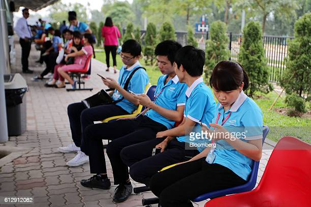 Workers use mobile phones while waiting for company buses at the Samsung Electronics Vietnam Co Plant at Yen Phong Industrial Park in Bac Ninh...