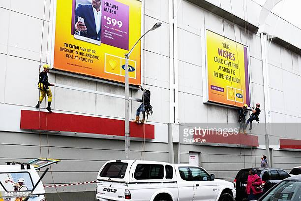 Workers use mountaineering techniques to position billboards at shopping center