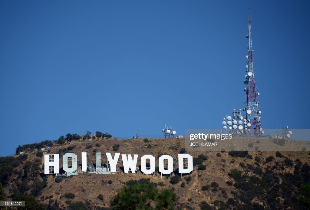 Workers use window-cleaner style platforms as they strip down the 50-foot (15-meter) tall letters, power washing the corrugated iron and apply nearly 400 gallons of fresh paint while restoring the Hollywood sign on October 26,2012 in Hollywood, California. The iconic Hollywood sign overlooking Tinseltown is getting its biggest renovation for 35 years, to prepare it for its 90th birthday next year. The operation, which started earlier this month, will take 8-10 weeks to restore the sign to its bright white glory atop Mount Lee in the Hollywood Hills north of Los Angeles. AFP PHOTO / JOE KLAMAR