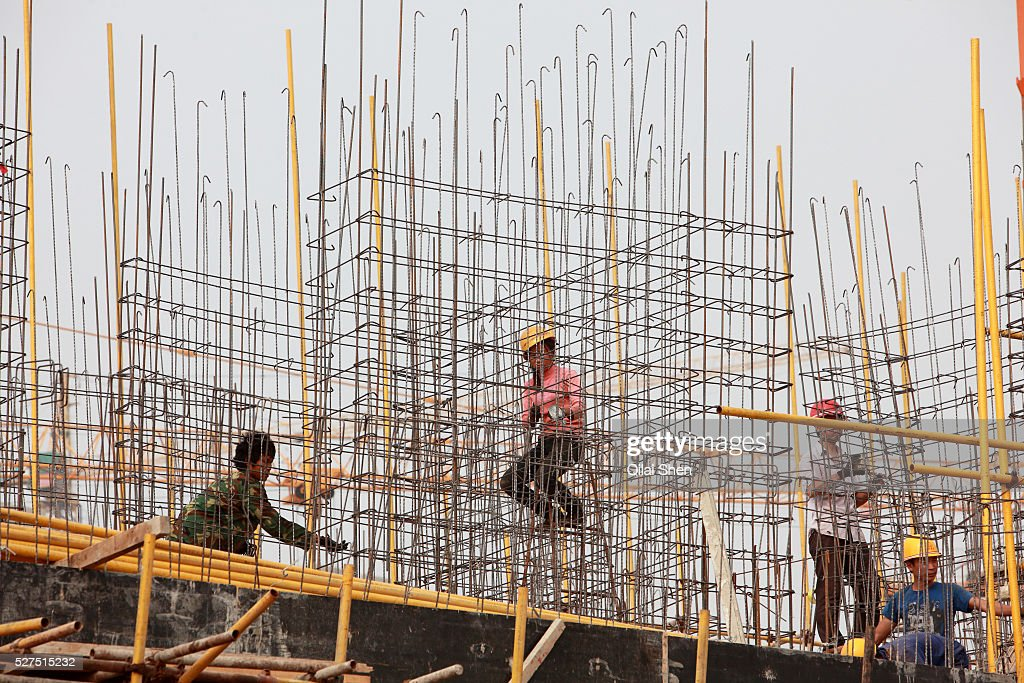 Workers use wires and steel rebars to build the skeleton of a building on the site of a new apartment development on the outskirts of Yulin Shaanxi...
