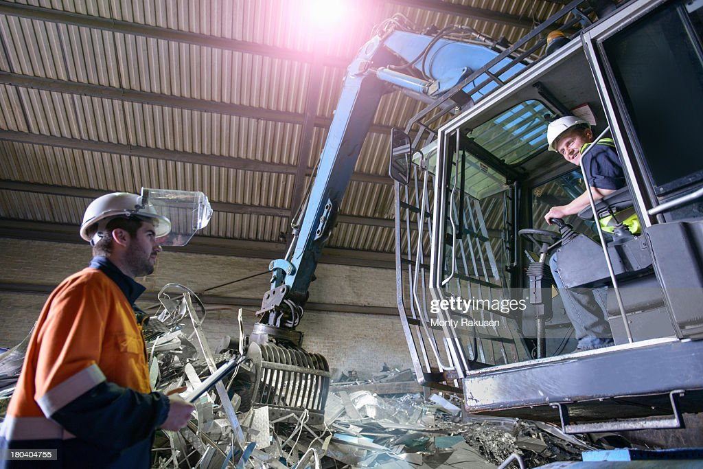 Workers using crane in scrapheap of aluminium recycling plant, low angle view