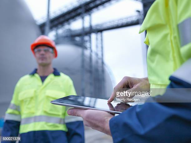 Workers using digital tablet at biomass facility, close up