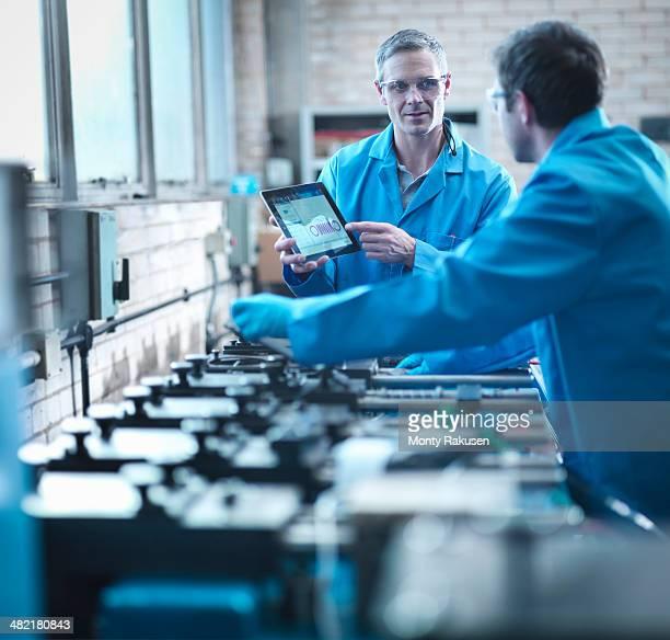 Workers using digital tablet for testing springs in laboratory