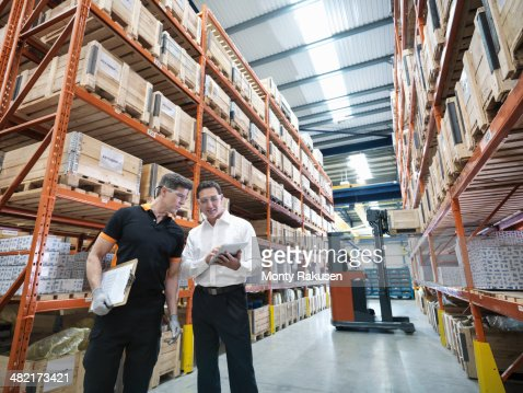 Workers using digital tablet in parts store in factory