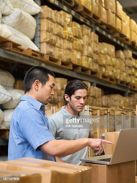 Workers using laptop in textile factory
