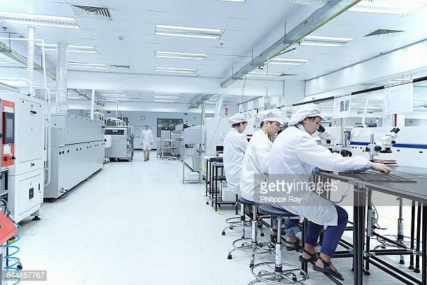 Workers using microscopes in factory that specialises in creating functional circuits on flexible surfaces