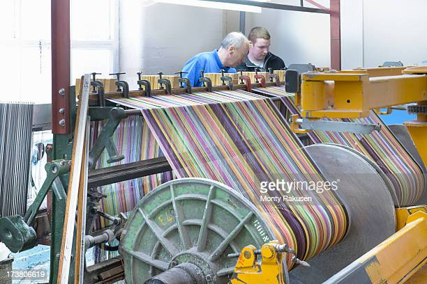 Workers using multicoloured thread on industrial loom in textile mill
