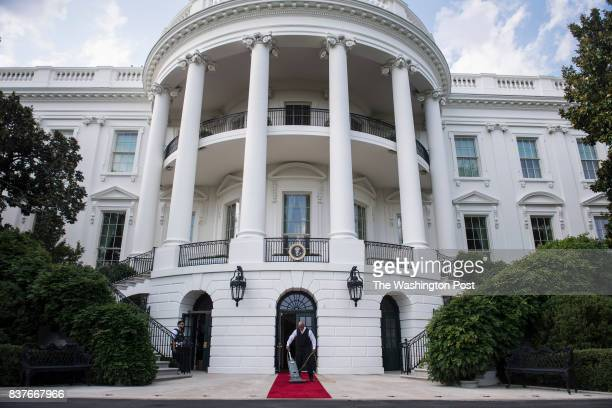 A workers vacuums a red carpet before President Donald Trump and First Lady Melania Trump receive South Korean President Moon Jaein and his wife Kim...