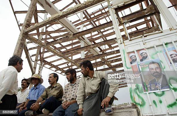 Workers wait for employers to hire them by campaign posters for parliamentary candidates on the door of a ruined house in the earthquakedevastated...