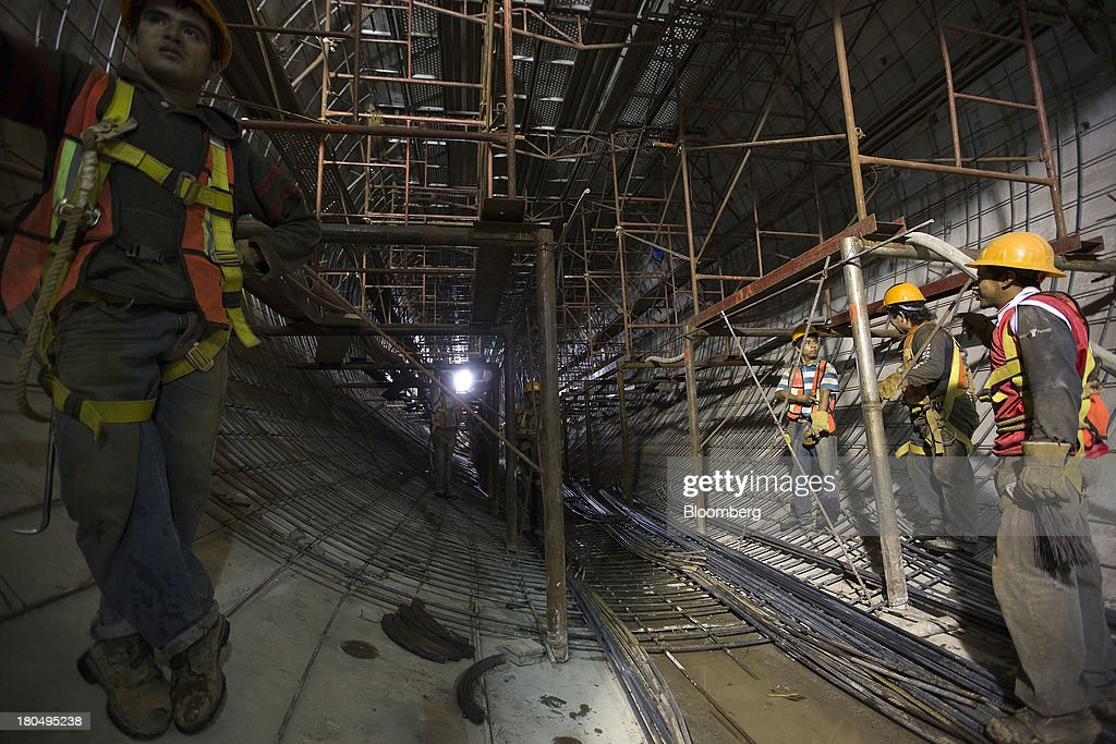 Workers wait for steel rods to be delivered inside the Tunnel Emisor Oriente (TEO), or Eastern Discharge Tunnel, during construction of the 38 mile (62km) underground wastewater treatment tunnel in Mexico City, Mexico, on Thursday, Sept. 12, 2013. The tunnel, which is expected to be completed in 2014, will boost Mexico City's drainage capacity to help prevent flooding during rainy season and the over-exploitation of groundwater resources. The project is being managed by Mexico's National Water Commission, Conagua. Photographer: Susana Gonzalez/Bloomberg via Getty Images