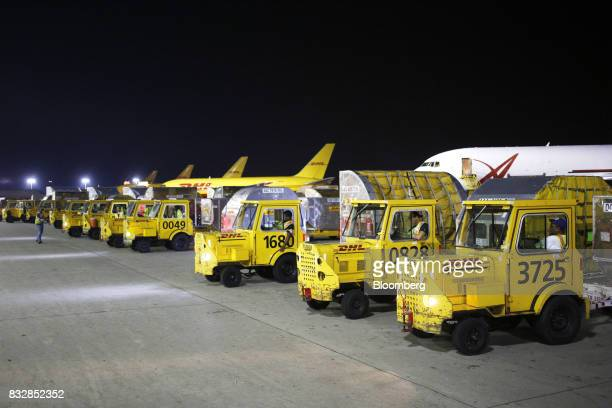 Workers wait to transport package containers at the DHL Worldwide Express hub of Cincinnati/Northern Kentucky International Airport in Hebron...