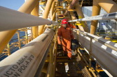 Workers walk across a connecting bridge on the Petroleos Mexicanos PolA Platform complex located on the continental shelf in the Gulf of Mexico 70...