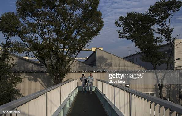 Workers walk along a pedestrian overpass outside the Toyota Motor Corp Motomachi plant in Toyota City Aichi Japan on Friday Oct 14 2016 Toyota plans...