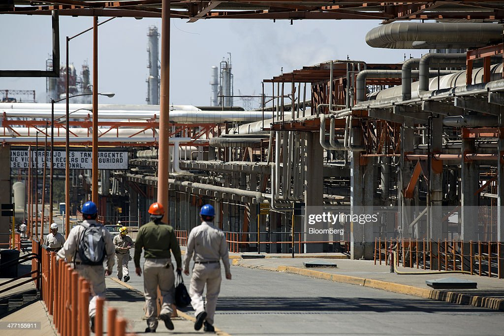 Workers walk along a road during a shift change at the Petroleos Mexicanos Miguel Hidalgo Refinery in Tula de Allende Mexico on Thursday March 6 2014...