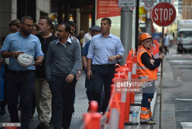 Workers walk along a street in the central business district of Sydney on April 19 2017 Australia's controversial decision to scrap a visa programme...