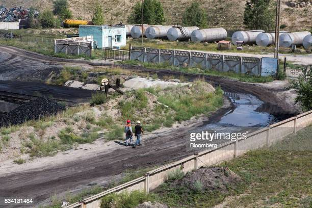 Workers walk along a track at the Darkhan Metallurgical Plant in Darkhan Mongolia on Monday Aug 14 2017 Mongolia desperate to make more of its...