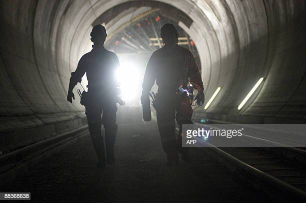 Workers walk along the 57kilometre railway tunnel under construction in the Alps at Sedrun on May 6 2009 The new St Gotthard tunnel is expected to be...