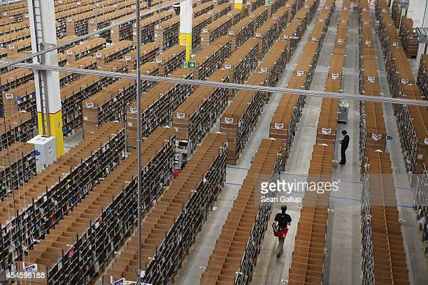 Workers walk among shelves lined with goods at an Amazon warehouse on September 4 2014 in Brieselang Germany Germany is online retailer Amazon's...