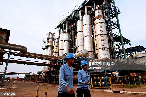 Workers walk at an ethanol distillation plant on the Jalles Machado SA sugarcane farm in Goianesia about 135 miles from Brasilia Brazil on Tuesday...