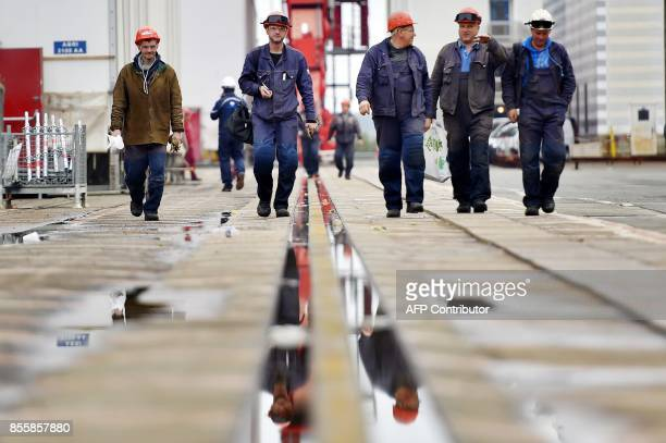Workers walk at the site of French shipyard STX in SaintNazaire western France on September 28 2017 French shipyard STX under an agreement thrashed...