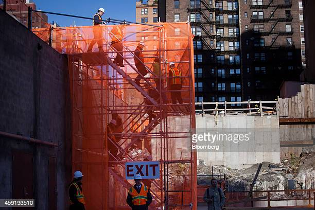 Workers walk down stairs to the completed Brookfield Office Properties Inc Manhattan West deck platform that covers the railroad tracks leading to...