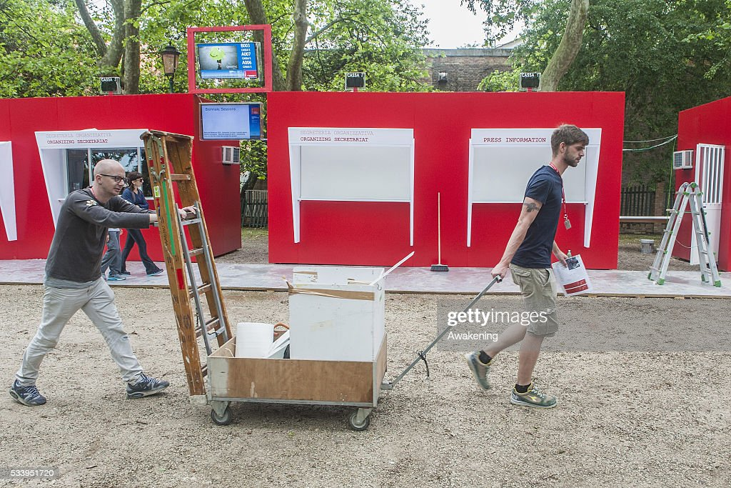 Workers walk in front of street signs of the 15th Architecture Venice Biennale near the Giardini area on May 24, 2016 in Venice, Italy. The 56th International Architecture Exhibition of La Biennale di Venezia will be open to the public from May 28, 2016 in Venice, Italy.