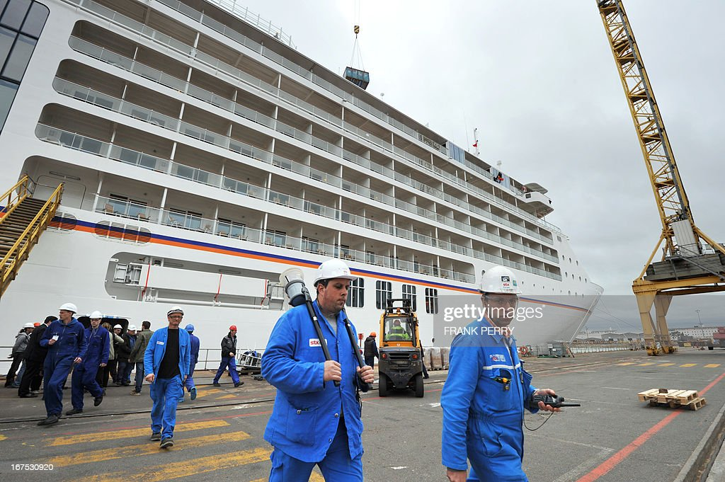 Workers walk in front of the luxury Europa 2 cruise liner is moored at the STX Europe shipyard in Saint Nazaire on April 26, 2013. The ship has been handed today to her German shipowner Hapag Lloyd Cruises.