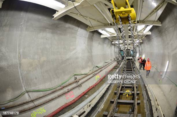Workers walk inside the tunnel boring machine of the new highspeed TAV rail line in the Chiomonte tunnel on November 122013 The highspeed rail link...