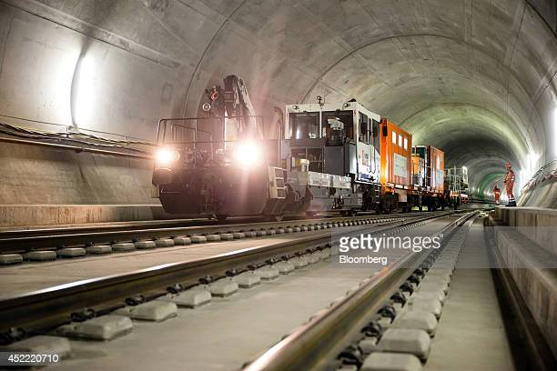 Workers walk near a support train inside the east section of the Gotthard Base Tunnel in Faido Switzerland on Tuesday July 15 2014 Drilling and...