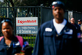 Workers walk near an entrance to the Exxon Mobil Corp Torrance refinery after an explosion and fire in Los Angeles California US on Wednesday Feb 18...
