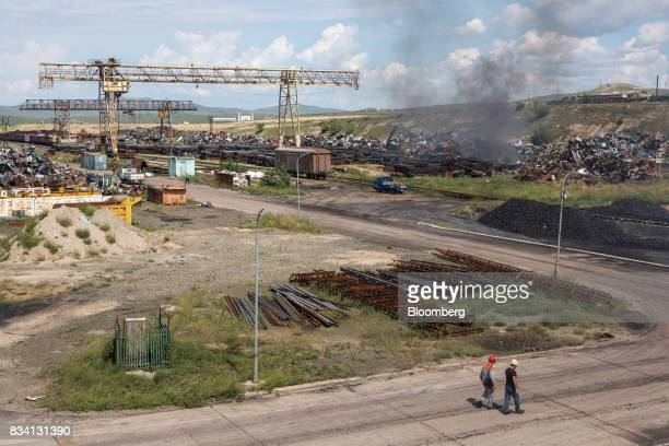 Workers walk near scrap metal at the Darkhan Metallurgical Plant in Darkhan Mongolia on Monday Aug 14 2017 Mongolia desperate to make more of its...