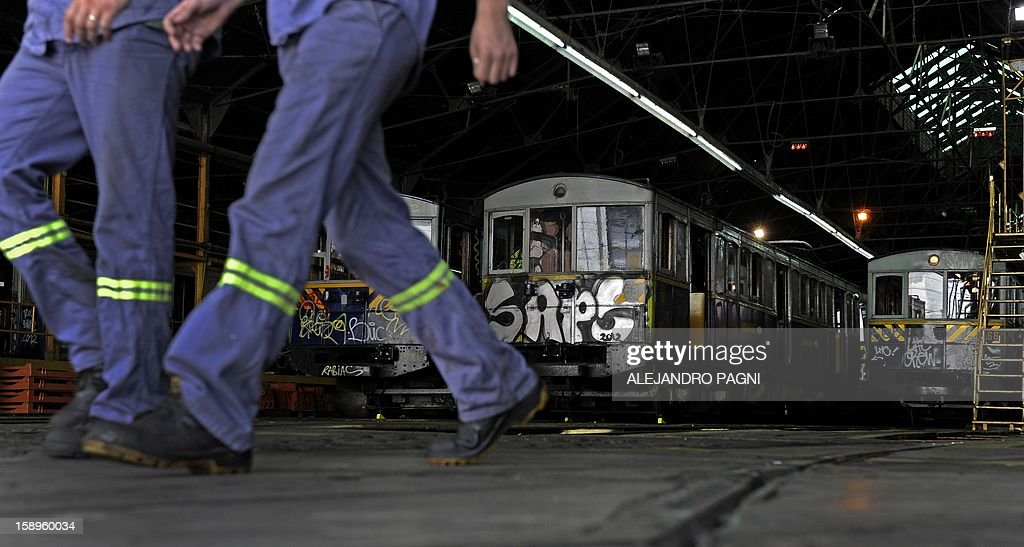 Workers walk next to the historic wagons of La Brugeoise at the garage El Polvorin, in the neighborhood of Caballito, Buenos Aires on January 4, 2013. The Line A will be closed betwen January 12 and March 8 following a decision by Buenos Aires city Mayor Mauricio Macri to replace the fleet with Chinese-made wagons. Line A was the first subway line to work in the southern hemisphere and its trains are among the ten oldest still working daily. The La Brugeoise wagons were constructed between 1912 and 1919 by La Brugeoise et Nicaise et Delcuve in Belgium.