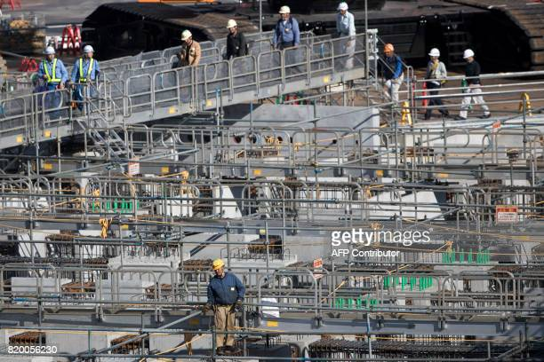 Workers walk on a bridge at the construction site for the National Stadium venue for the upcoming Tokyo 2020 Olympic Games in Tokyo on July 21 2017...
