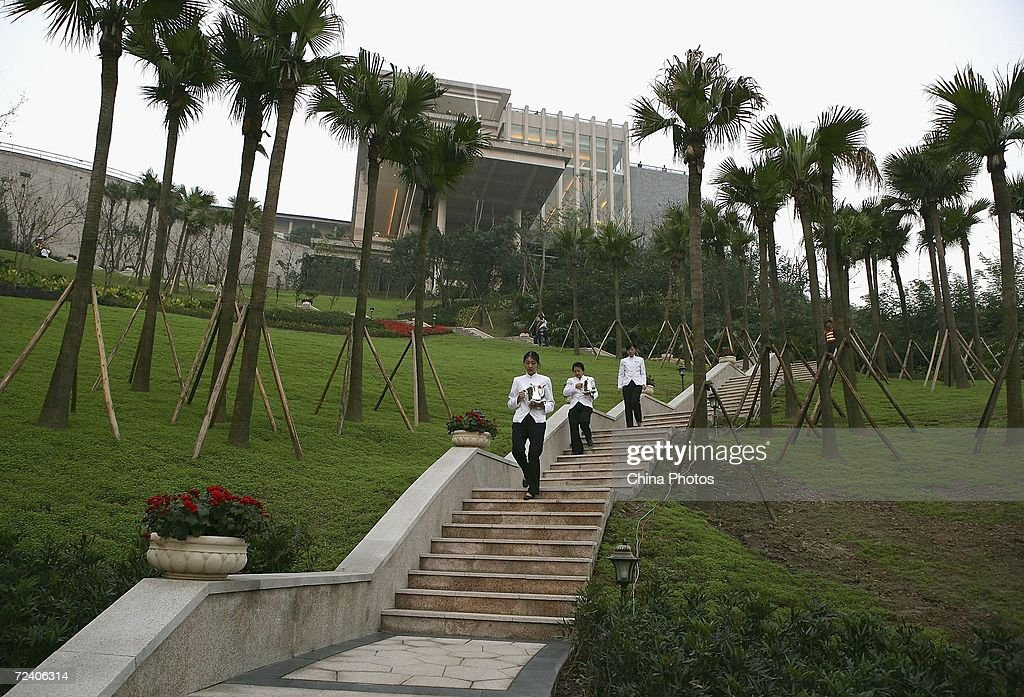 Workers walk on a path during the opening ceremony of Chongqing Palm Springs Garden villa on November 3 2006 in Chongqing Municipality China The...