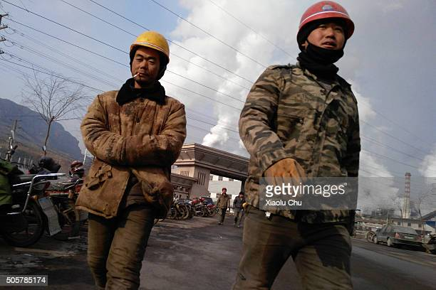 Workers walk out the main gate of Qian'an steelworks of Shougang Corporation on January 20 2016 in Tangshan China Shougang Corporation is one of the...