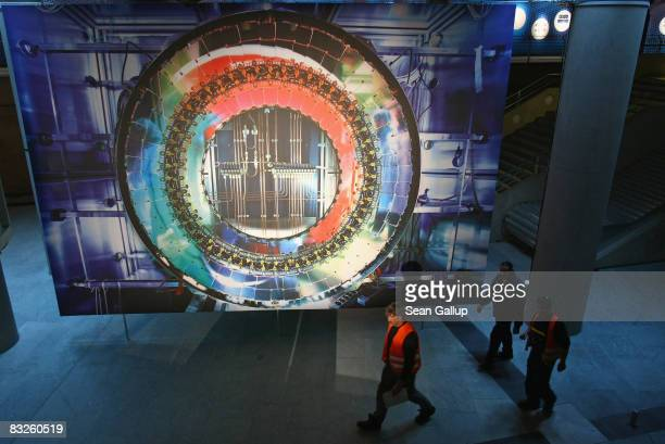 Workers walk past a giant photograph of a part of the Large Hadron Collider at the 'Weltmaschine ' exhibition on October 14 2008 in Berlin Germany...